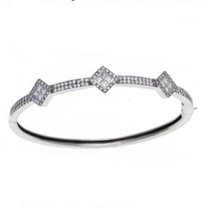 An 18 karat white gold bangle bracelet set with Princess and Round cut diamonds