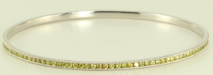 Yellow diamonds stand out on this 14 karat white gold diamond bangle bracelet