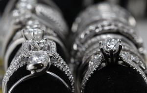 A row of 14 karat white gold rings set for display.